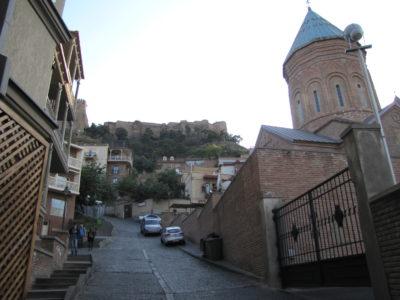 Une rue du centre-ville avec, au fond, la forteresse Narikala.